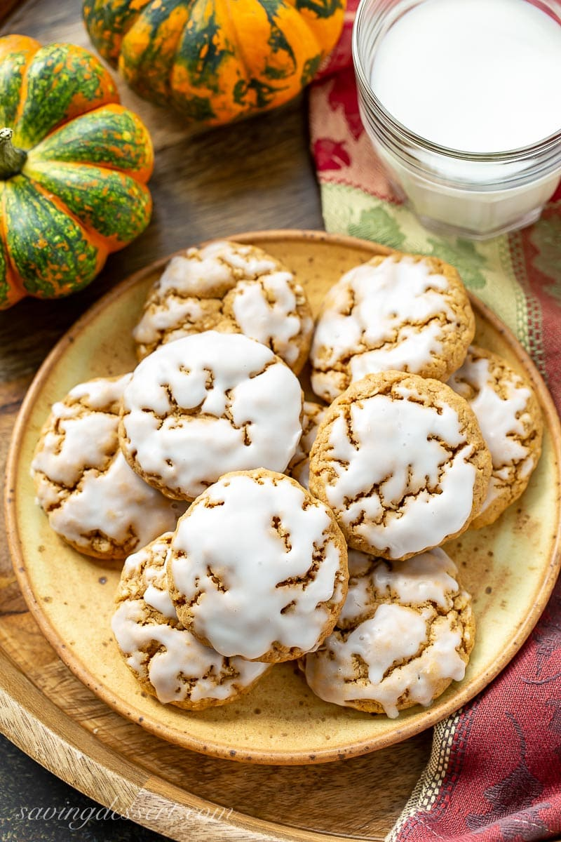 A plate of iced pumpkin oatmeal cookies and a glass of milk