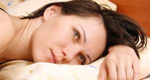 žena leži na krevetu