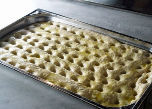 After the focaccia doubled in size in the pan, we indented it with our fingers and covered it in olive oil, then popped it in the oven.