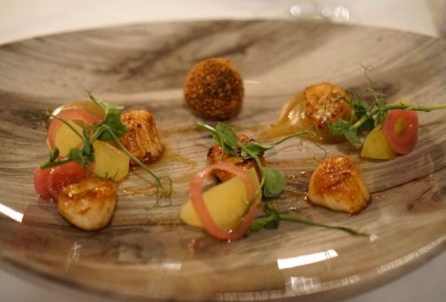 Seared scallops with black pudding, apple, cider dressing, and pickled shallots