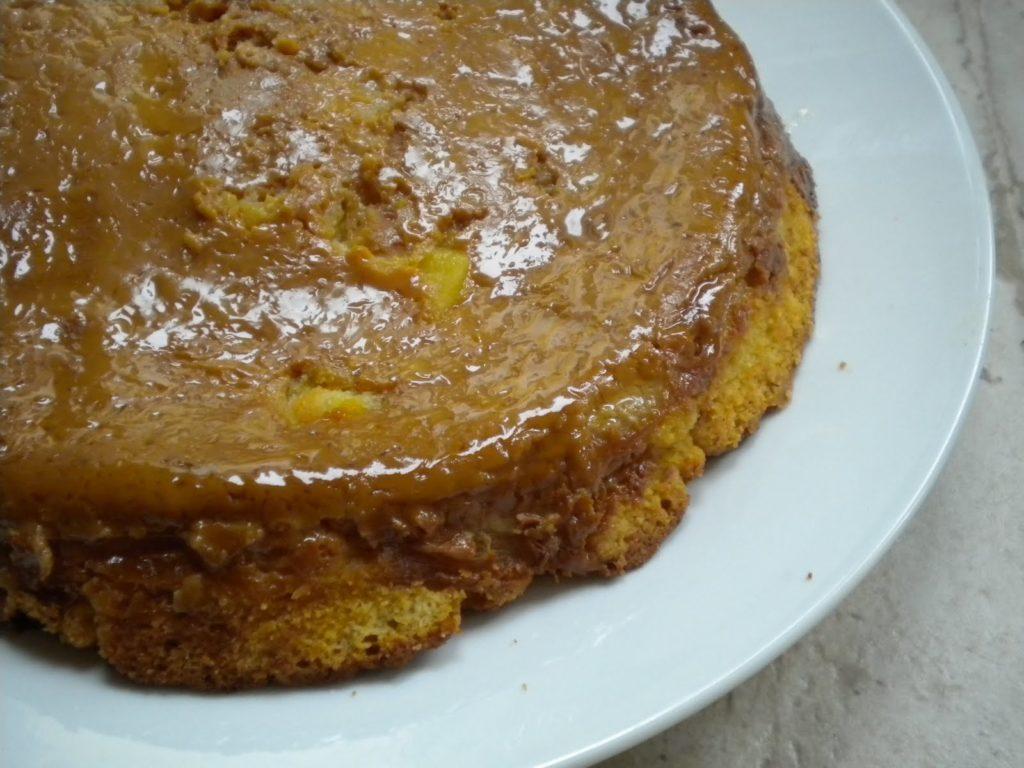 Upside-Down Dulce de Leche Organic Apple Cake on white serving plate.