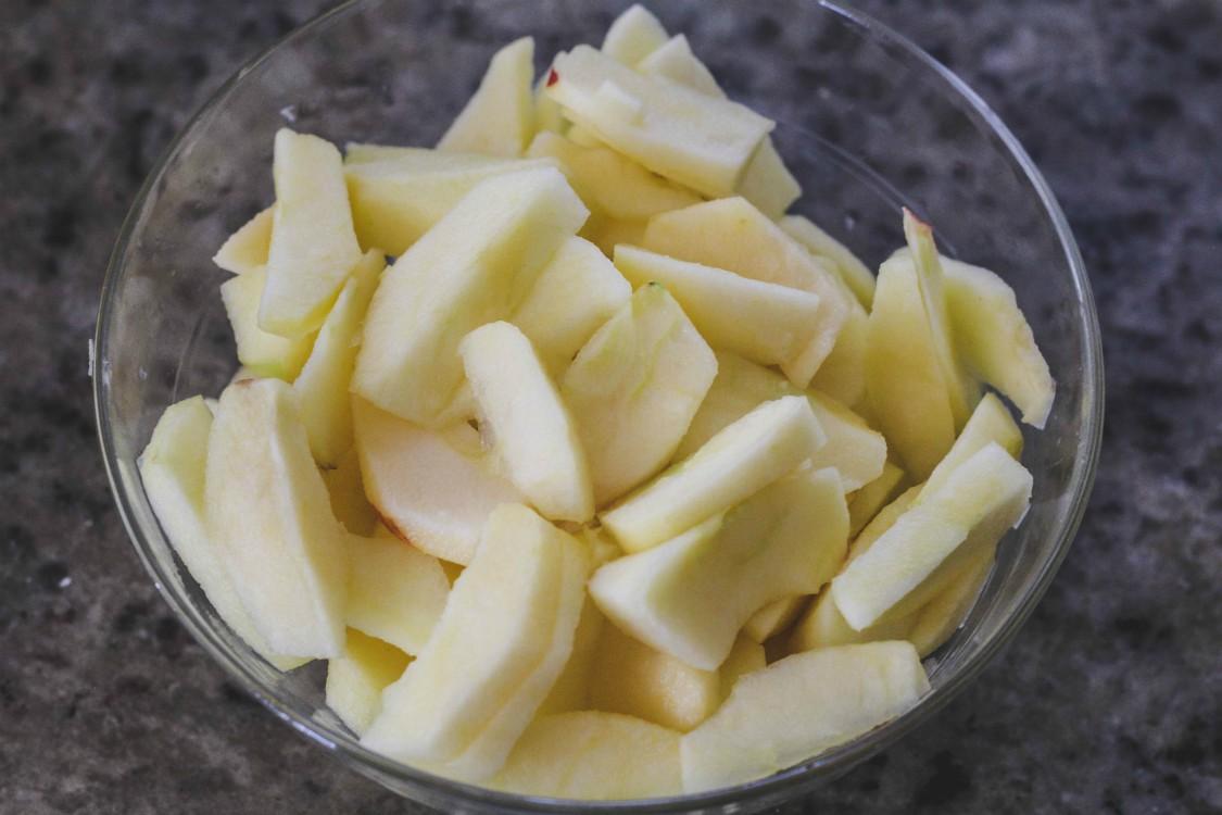 overehead image of apple slicesi in glass bowl