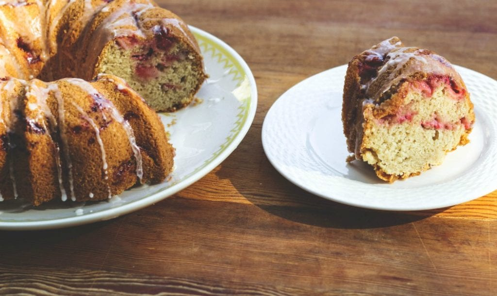 slice of fresh strawberry cake on plate next to larger bundt cake