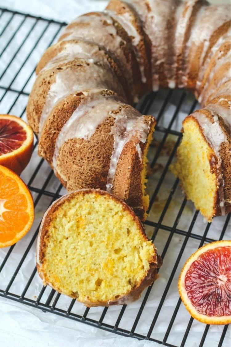 overhead image of a orange bundt cake with orange glaze on baking rack sliced open