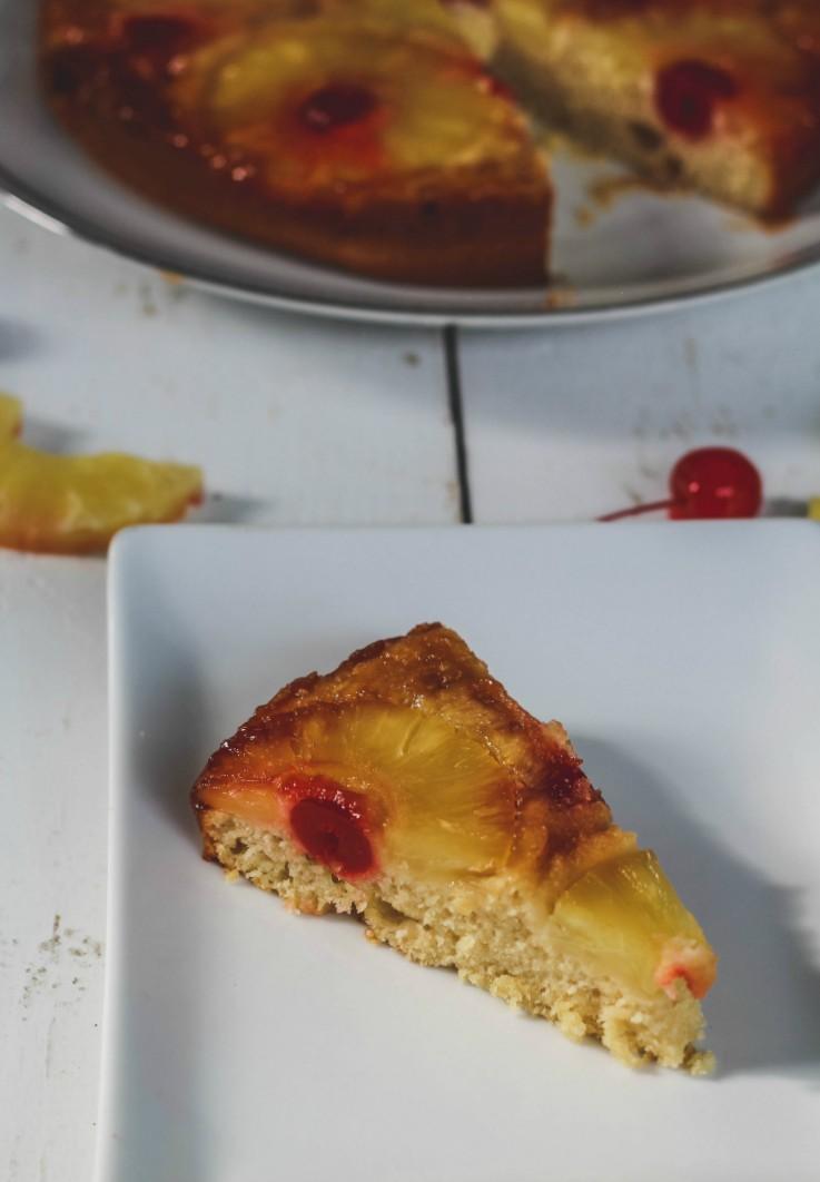 slice of vegan pineapple upside down cake on white plate