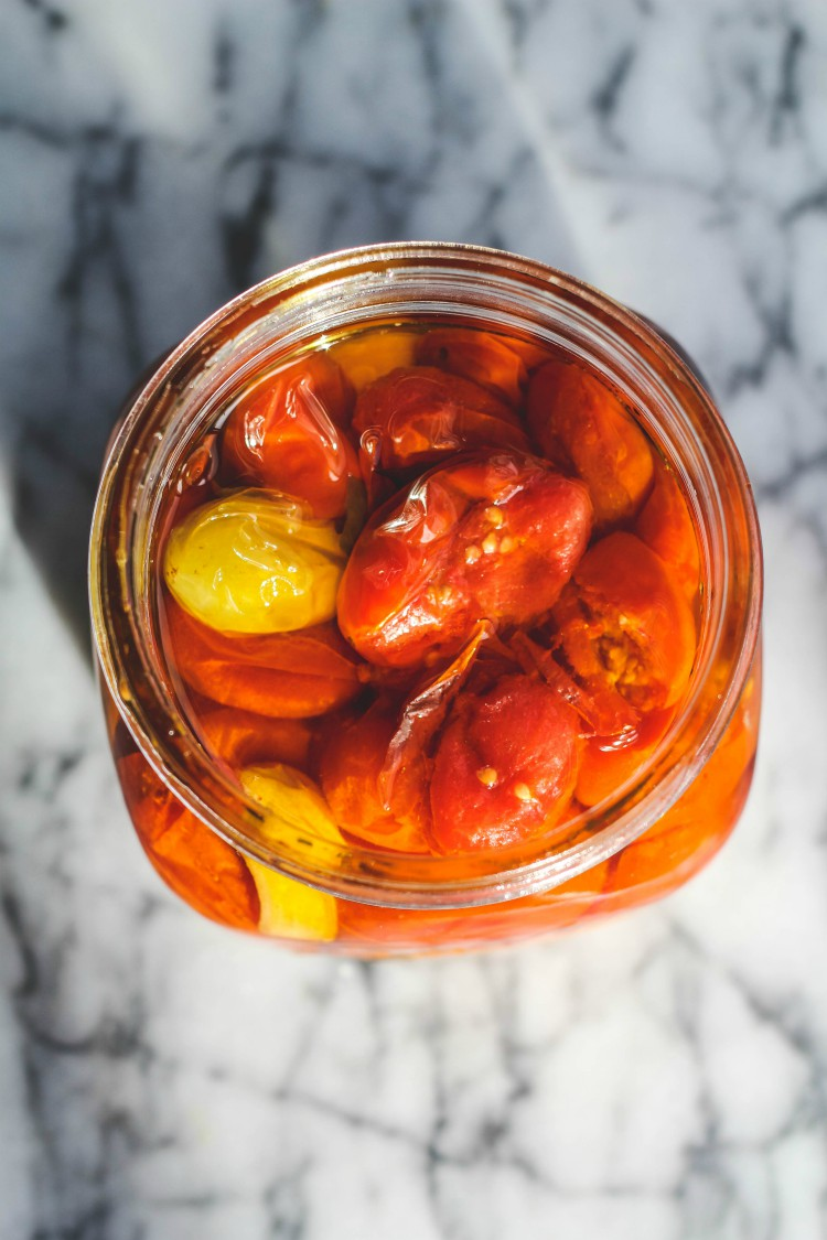 overhead image of cherry tomato confit in a jar