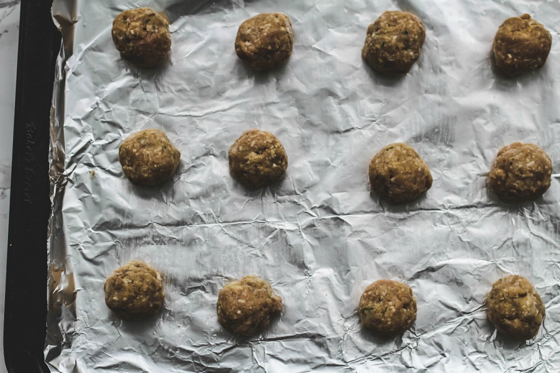 overhead image of meatballs on a lined baking pan