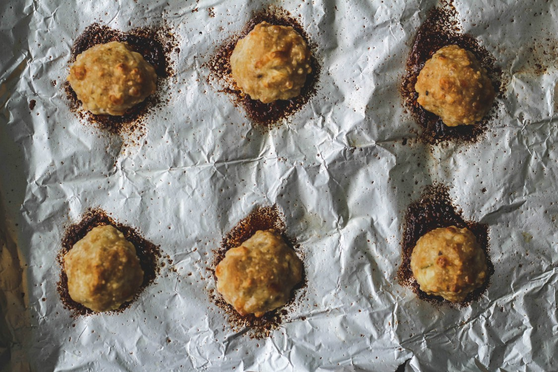 overhead image of meatballs baked on a foil lined sheet