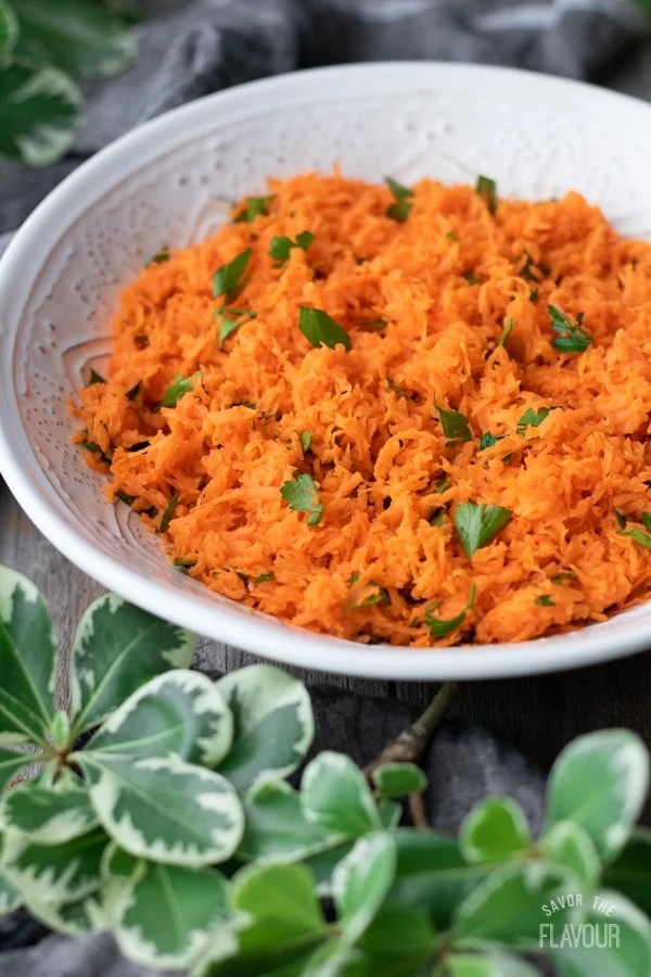 white bowl of French grated carrot salad with greenery