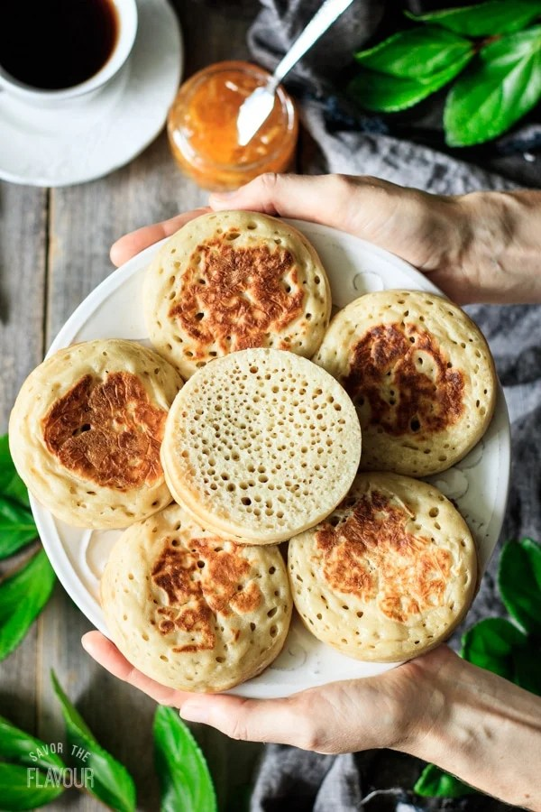 person holding a white plate of English crumpets