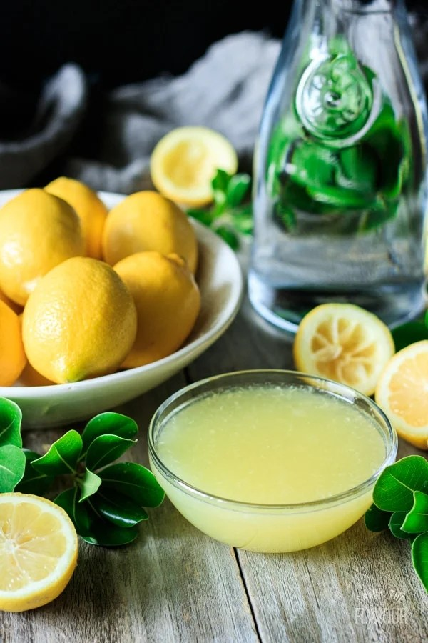 bowl of lemon juice with fresh lemons and water