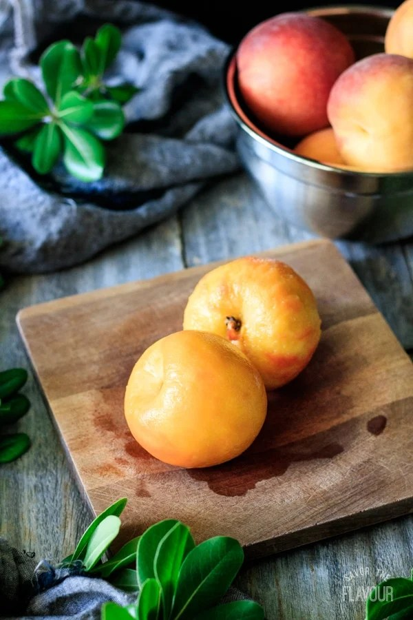 two peeled peaches on a wooden cutting board