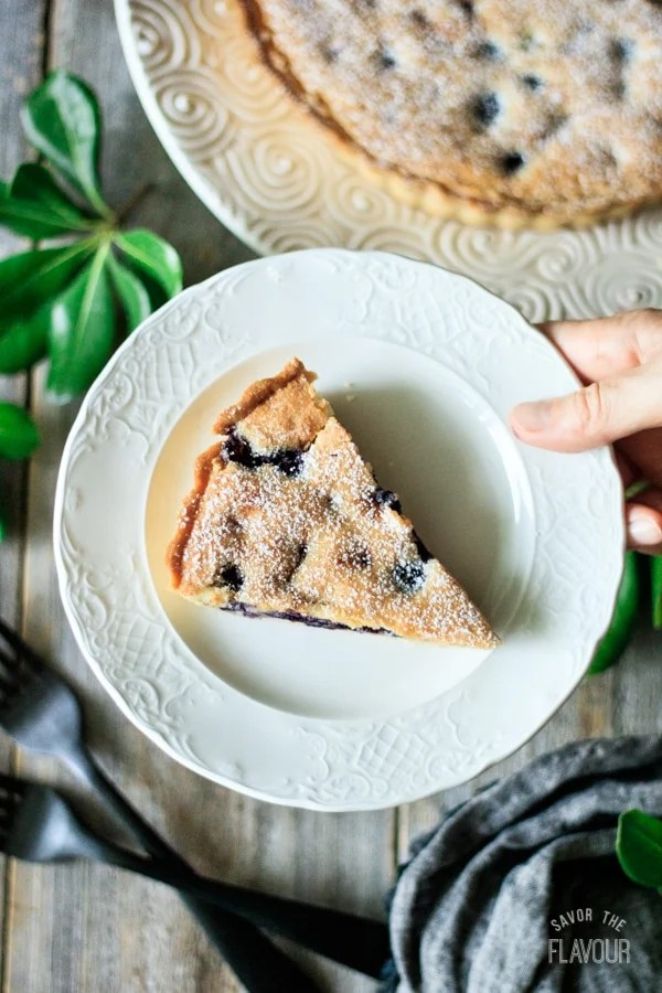 holding a slice of blueberry frangipane tart on a plate