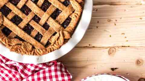 top down view on vegan cherry pie with red checkered tablecloth and white plates