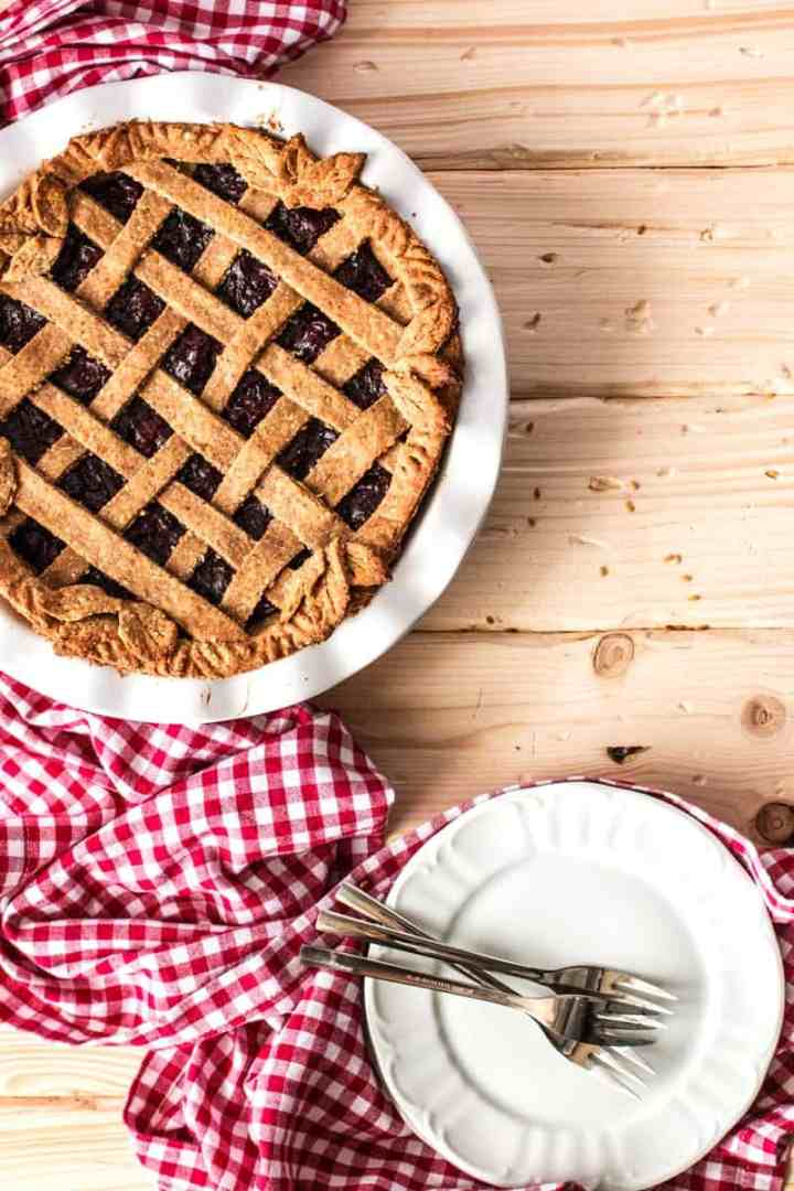 top down view on vegan cherry pie next to white plates with a red white checkered tablecloth