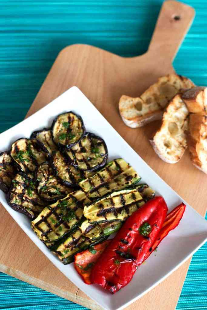 wooden board on blue mat with plate filled with grilled vegetables