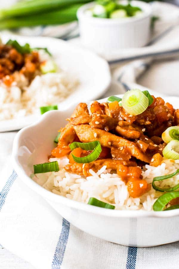 close up photo of apricot chicken in a bowl with rice