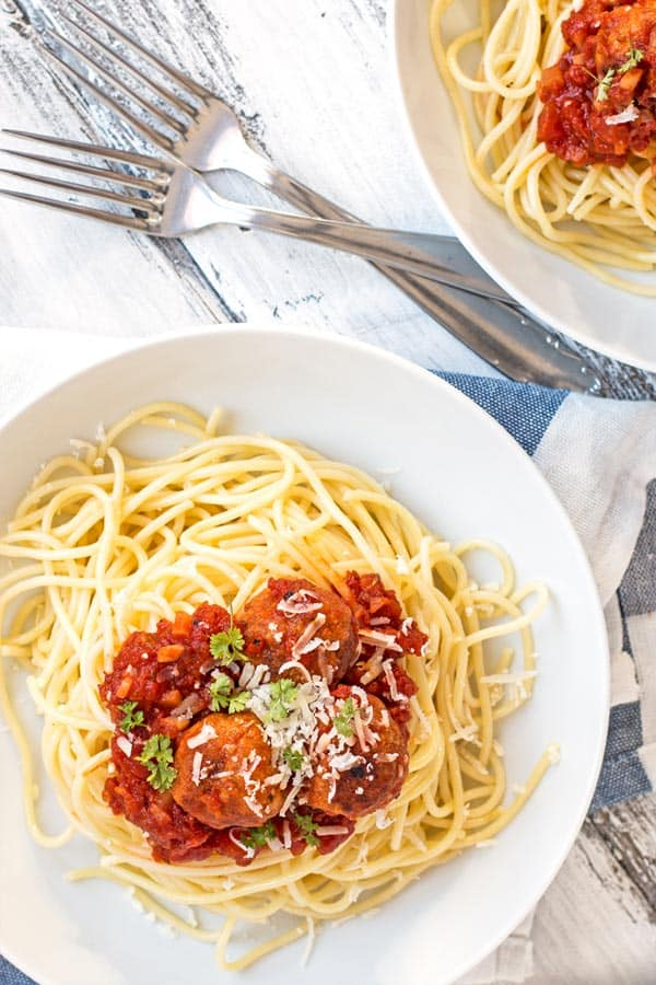two white plates with forks, filled with spaghetti, tomato sauce and turkey meatballs