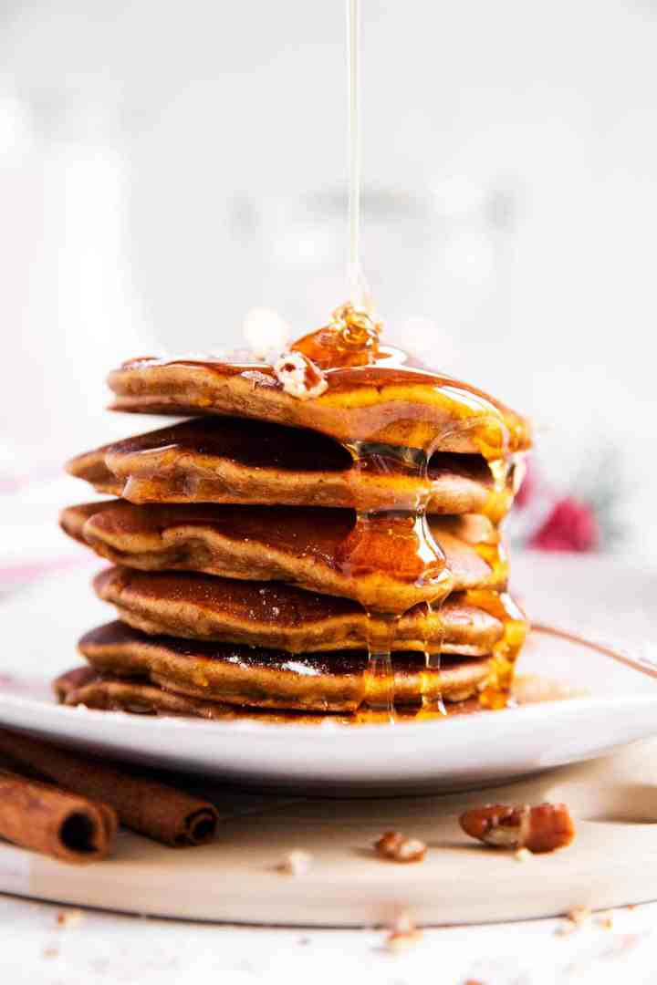 stack of gingerbread pancakes with maple syrup drizzling over