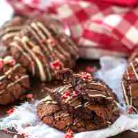 You will love baking up a storm this Christmas with this recipe for Peppermint Brownie Cookies! Deliciously chewy and fudgey cookies full of cocoa flavors are drizzled with chocolate and topped with red and white candies! The perfect holiday treat!