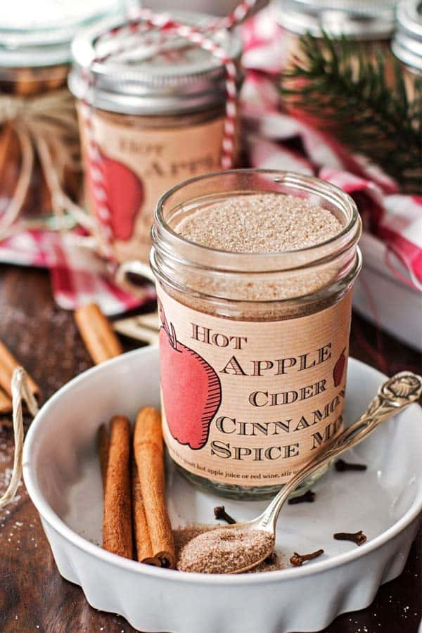 open jar with apple cider spice mix on a Christmas decorated table