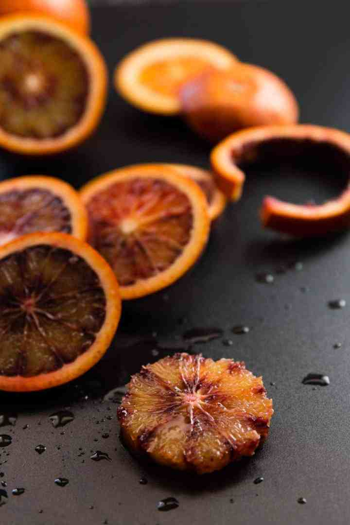 frontal view of sliced blood oranges on black cutting board