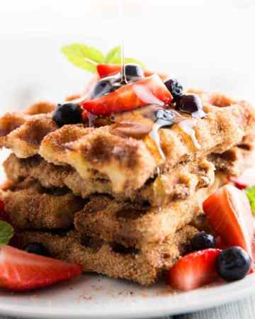 stack of french toast waffles topped with fresh berries and drizzled with maple syrup