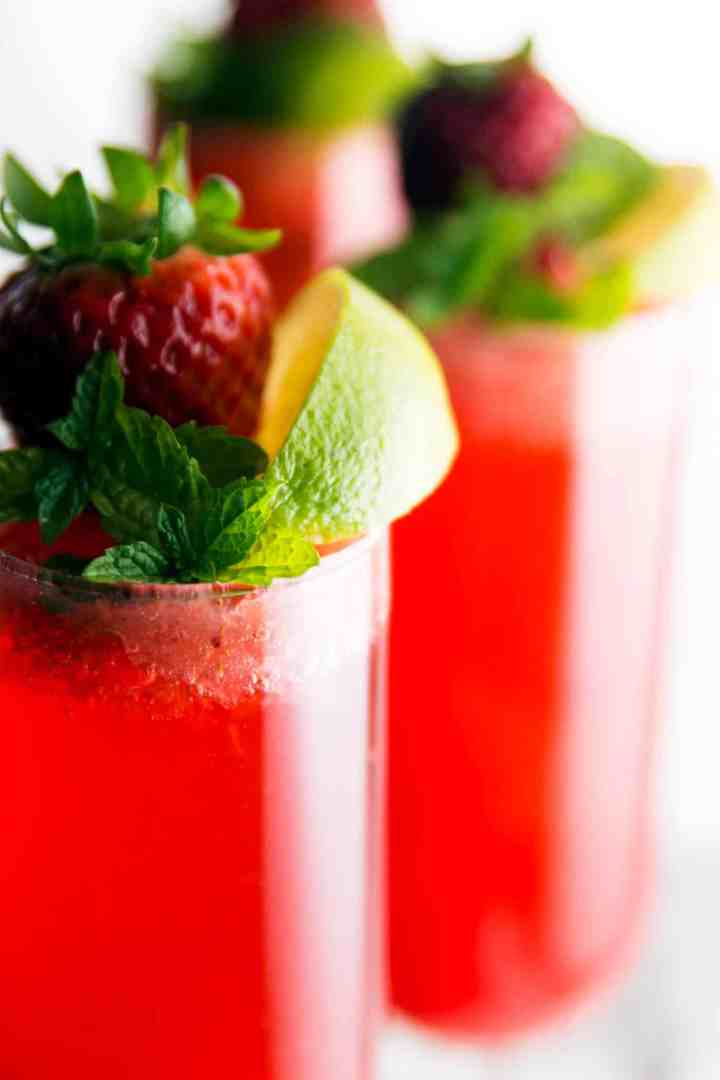 close up photo of champagne glasses filled with strawberry cocktail and garnished with lime, mint and fresh strawberry