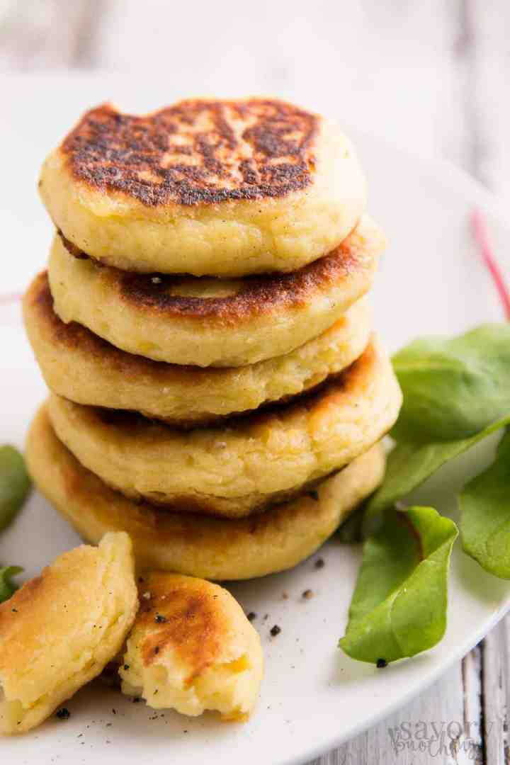 stack of mashed potato pancakes on a plate with salad greens on the side
