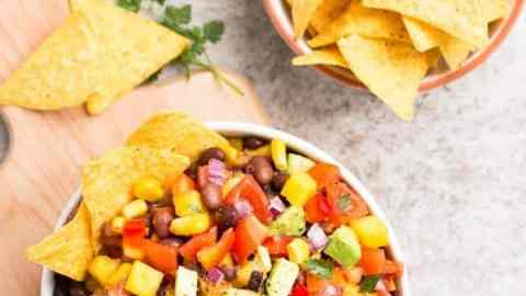 top down view on tablescape with mango avocado black bean salsa, tortilla chips and lime
