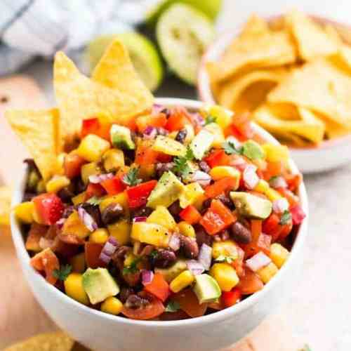 avocado mango salsa in white bowl with tortilla chips in background