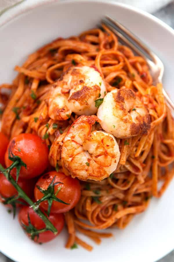 A simple but impressive garlic butter shrimp pasta recipe. Everything is tossed in a delicious homemade tomato sauce, easy for weeknight dinners but elegant enough for guests as well!