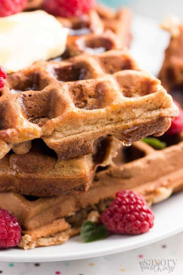 close up photo of a stack of oatmeal waffles with bananas and raspberries around