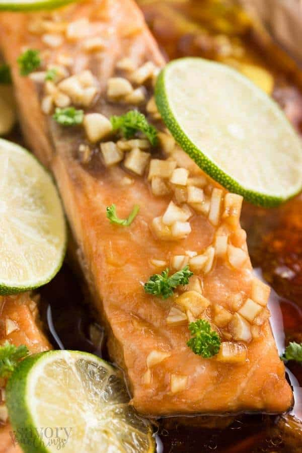 close up photo of salmon fillet with lime slices and chopped garlic