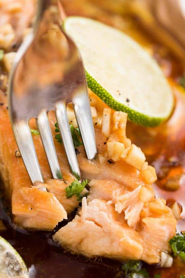 Fork in a piece of baked salmon