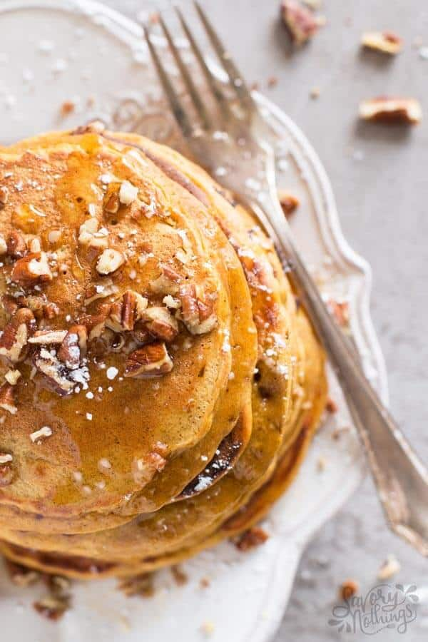 Fluffy pumpkin pancakes covered with chopped pecans and maple syrup.
