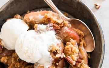 easy apple crisp in a bowl with a spoon and ice cream