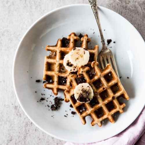 top down view on two banana waffles on white plate with a fork