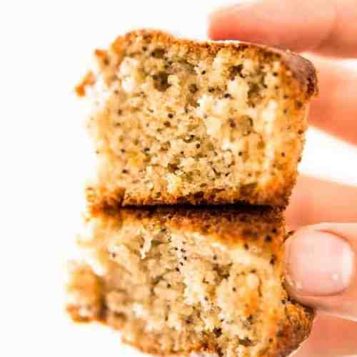 female hand holding lemon poppy seed muffin sliced in half