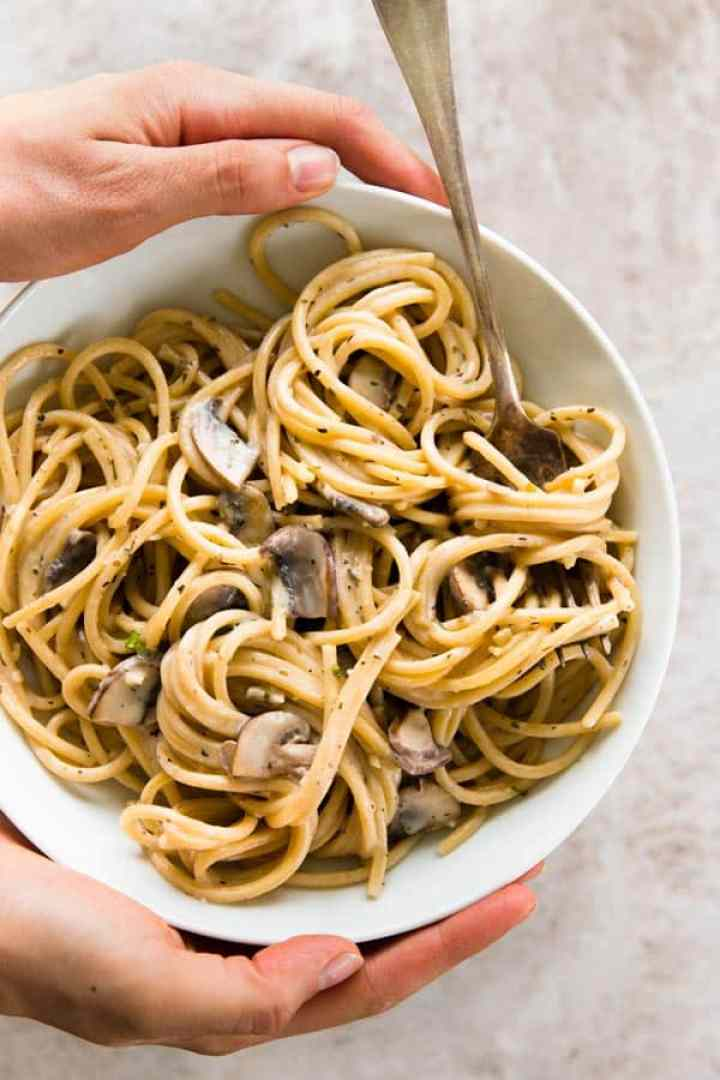female hands holding mushroom pasta in white bowl with fork