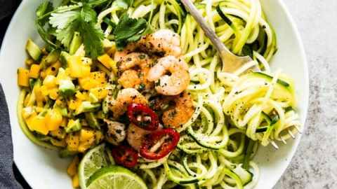 overhead view on white plate with zucchini noodles and shrimp
