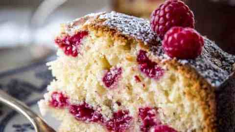 slice of raspberry cake on floral plate with fresh raspberries and silver fork