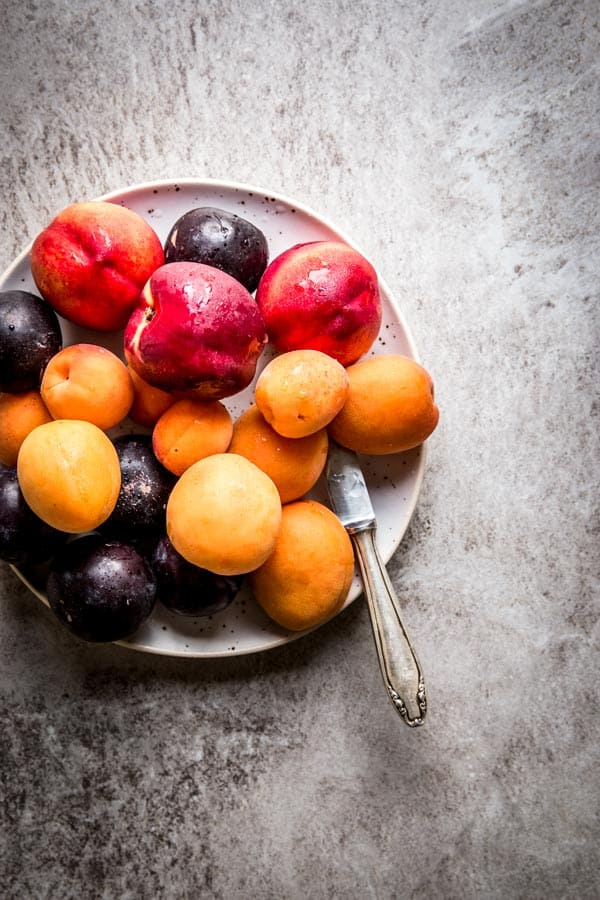 Stone fruit on a pottery plate. On the table with a knife, ready for slicing, still life.