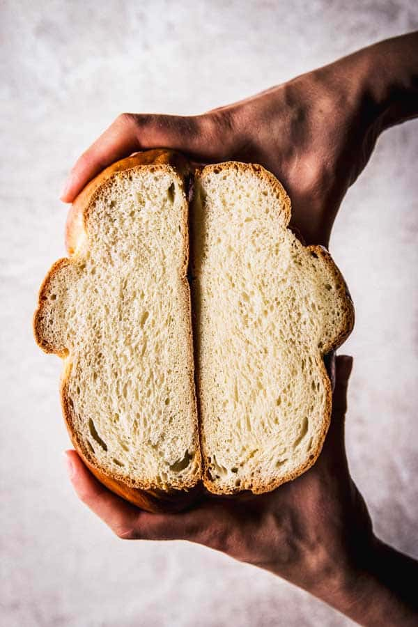 top down view on female hands holding sliced open braided bread
