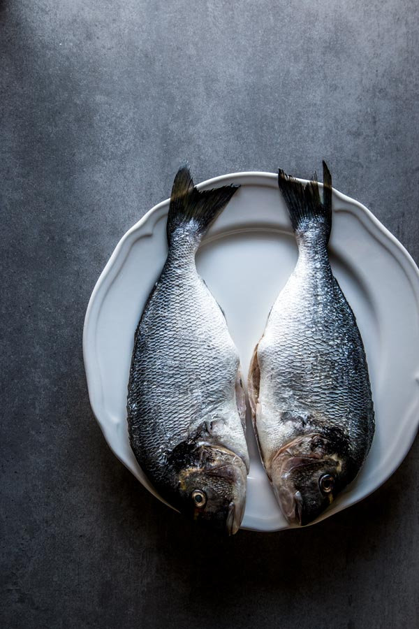 Whole sea bream, gutted and scaled. Beautiful still life food photography and styling.