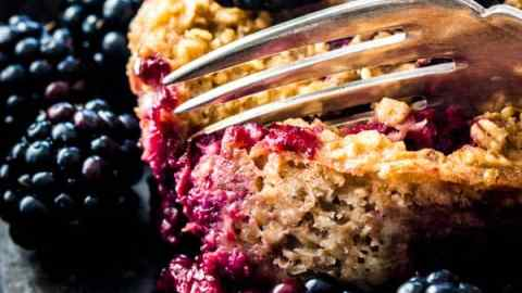 close up of fork digging into blackberry oatmeal cup