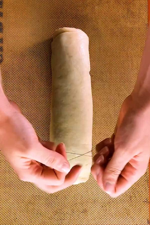 cutting a log of dough into cinnamon rolls with a pice of string - 2