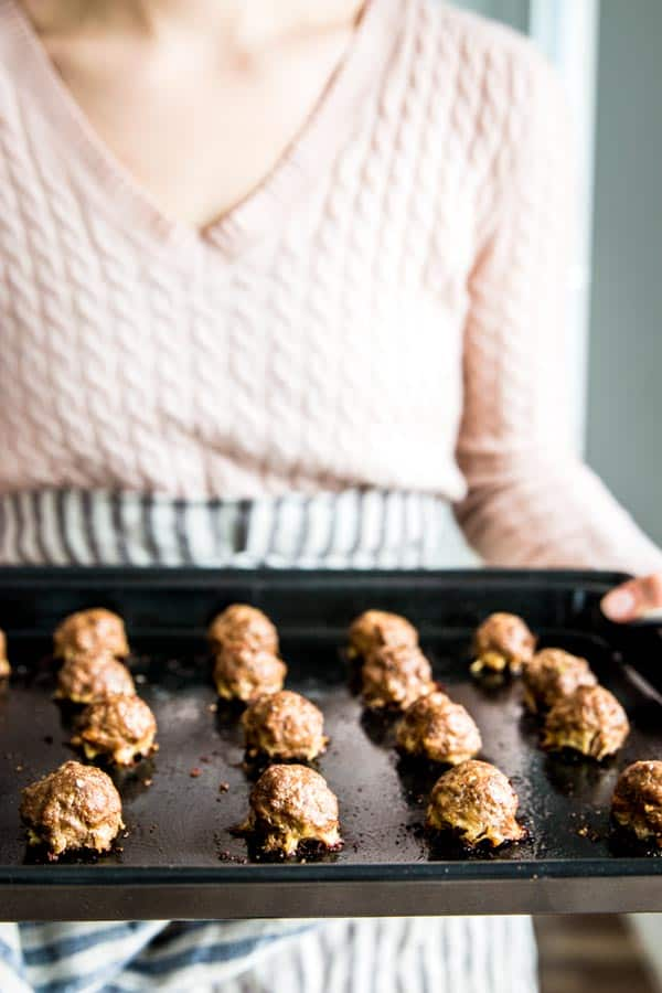 Holding oven baked meatballs on a tray.