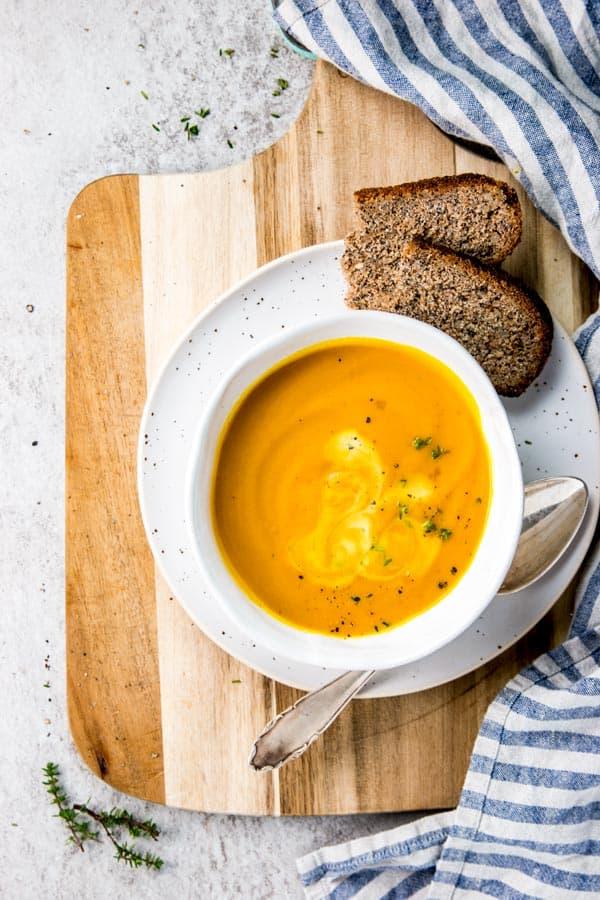 pumpkin soup in white bowl on wooden board