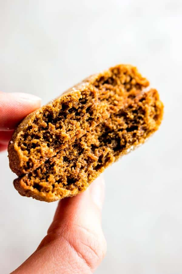 female hand holding a molasses cookie broken in half